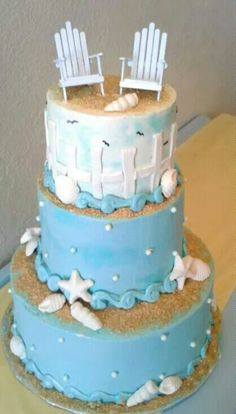 Beach wedding cake with shells, Adirondack chairs, beach fence, sand and waves