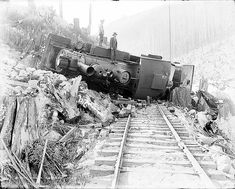 Two men standing atop wrecked locomotive on the Great Northern Railway tracks, 1926