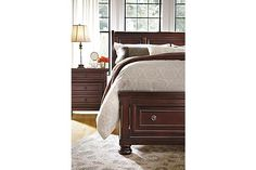 """The Porter Sleigh Bed from Ashley Furniture HomeStore (AFHS.com). The warm rustic beauty of the """"Porter"""" bedroom collection uses a deep finish and ornate details to create an inviting furniture collection that fits comfortably into any bedroom decor."""