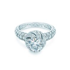 This round brilliant center stone complemented <br>by pavé-set diamonds was inspired by the simple <br>beauty of flower buds.