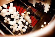 Balloons on different lengths of string by the staircase- this is exactly what I am going to have but with some pink heart balloons too