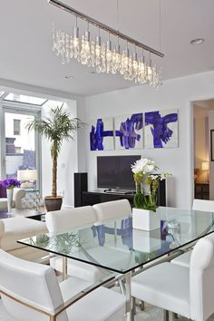 Chic dining room design with glass table and white leather chairs   Marie Burgos Design