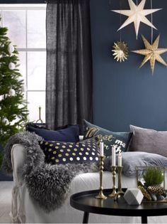 Scandinavian-style living room dressed up for Christmas. The touches of gold in the seasonal throw pillows give the room a holiday radiance. Products from ellos.se