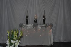 Unity Candle: The under tablecloth has twinkle lights underneath it. Then add a second tablecloth of pretty fabric, and pin it up in these drapes. Decorate the pinned places with bows, flowers, or jeweled accents. Notice too that the center candle is a globe candle, not a pillar. Lovely.