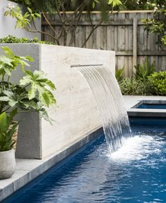 A travertine-clad water feature flows into the fibreglass swimming pool. Backyard Pool Landscaping, Backyard Pool Designs, Small Backyard Pools, Swimming Pools Backyard, Swimming Pool Designs, Swimming Pool Fountains, Swimming Pool Waterfall, Fiberglass Swimming Pools, Pool Water Features