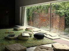 Loving the windows, the sea green rug and the pillows on the floor. Such a great room.