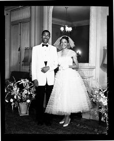 Bride and groom posed in front of a fireplace, 1956. Scurlock Studio.
