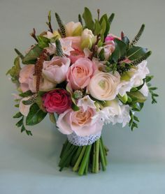 A Spring bridal bouquet, in pinks and creams. This bouquet contains tulips, ranunculus, paperwhites, catkins, pussy willow and foliage.