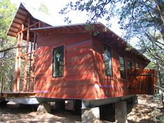 """The structure was built onto a concrete-and-steel base. At left is the porch, pre-screening; at right is a cantilevered outdoor shower off the bathroom. The exterior cladding is cedar, stained in four different colors then placed randomly """"for a different palette of colors, like a blend of bricks,"""" says Panton. """"The owner's favorite color is purple, so we added a purple board here and there."""""""