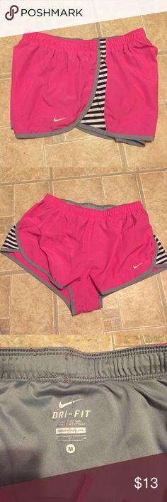 Nike Dri-fit shorts Pink Nike shorts with ack and whites stripes on the side. Not stains or flaws other than some wear on the print-on tag inside. Nike Shorts