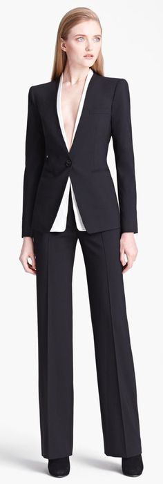 Armani Collection. Beautiful suit. Too bad that her make-up is warm and her lips are pale. She needs a bright fuchsia lipstick and old rose blusher for a healthier and friendlier look. She looks ill.