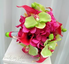 """The perfect beach wedding bouquet. This vibrant bouquet is designed with 8 hot pink real touch mini calla lilies, each bloom measures 2"""" by 3"""", along with 8 silk lime green orchids, blooms measuring 3"""" on a bed of fuchsia pink hydrangea. The handle treatment is wrapped with lime green"""