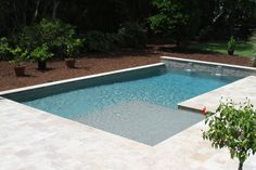 Geometric Swimming Pool with Water Features, a Sun Ledge, and Umbrella Hole