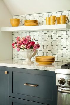 White and blue kitchen boasts white floating shelves over dark blue cabinets adorned with brass hardware paired with white quartz countertops as well as a white geometric tiled backsplash.