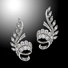 Platinum and diamond swirl ear clips, French, c. 1950s. A mix of both baguette and round brilliant diamonds are set into the foliate design. Gold clip backs, French hallmarks.