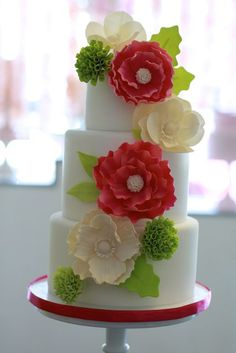 Coral and ivory flower cake with apple green accents.