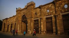 Children play soccer in front of an old buildingin the vast necropolis known as the City of the Dead in Cairo, Egypt, Friday, Oct. 10, 2014. The structure was originally built as a palace in Cairo's Garden City neighborhood in the 1820s. Its facade was moved to the current location in the early 1900s, remodeled as a home and served until it was abandoned. (AP Photo/Hassan Ammar)