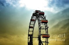 Historical Ferris Wheel.   A giant historical ferris wheel against a colorful sky. Low sun and rough weather changes the clouds and sky into a color bloom.   Location: Prater, Vienna Austria.
