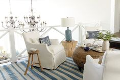 blue and white stripe rug, white slipcovers, wood accents, lots of white, wicker, blue lamp, navy and white pillows, greenery