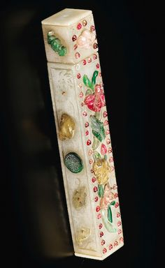 PALE CELADON JADE CASE INLAID QING DYNASTY, QIANLONG PERIOD   quadrangular, both sides inlaid with precious stones multicolored flowers and foliage and bats and shou characters. 13.5 cm, 5 3/8 in