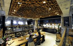 8 surprising Starbucks locations: A FORMER BANK VAULT Dutch designer Liz Muller transformed a bank vault in Amsterdam, Netherlands, into Starbucks's first concept store in Europe in 2012. The vault's original marble floors and concrete walls were left intact. More than 1,800 hand-cut wood blocks hang from the ceiling, shaping the face of the siren on the company's logo.