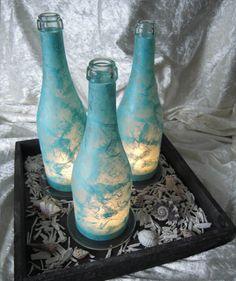 Flaschen-Windlichter in türkis auf Tablett mit Muscheln.