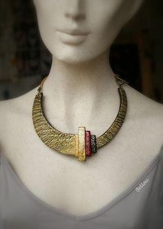 Un joli collier réalisé en argile polymère avec la technique du craquelé or sur noir. Tour de cou en nubuck doré, fermoir toggle (en T) en métal couleur bronze sur le coté.  - 18660852
