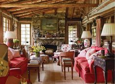 Toby West log cabin living OMG I love this room! All the red and the feminine touches are just perfectly juxtaposed against the rustic. Beautiful and exciting.