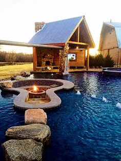Boulders serve as stepping stones across a shallow 'beach' area of this pool, to access a fire pit area with built-in benches placed in the center of the pool. Fire Pit Landscaping, Fire Pit Backyard, Backyard Pools, Indoor Pools, Amazing Swimming Pools, Cool Pools, Cabana, Outdoor Spaces, Outdoor Living