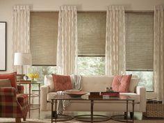 salon contemporain avec des stores, rideaux semi-transparents, canapé droit blanc et deux coussins rougeâtres
