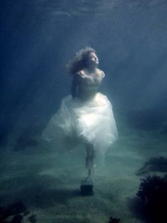 Woman wearing dress & chain to cement block underwater