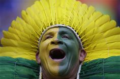 A Brazil supporter cheers for the national team before the group A World Cup soccer match between Cameroon and Brazil at the Estadio Nacional in Brasilia, Brazil