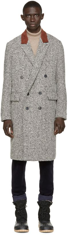 Long sleeve herringbone coat in black and white. Notched lapel collar trimmed in brown velvet. Buttonhole at lapel. Double-breasted button closure at front. Patch and flap pockets at front. Vented at back hem. Single-button barrel cuffs. Zip pockets at interior. Fully lined.