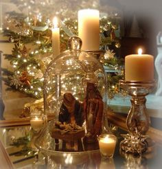 Mary and Joseph with baby Jesus in a glass bell jar with candles all around for Christmas decor.
