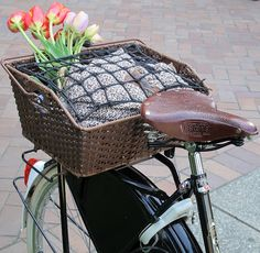 Vintage basket on the back of a bike with cushion and flowers