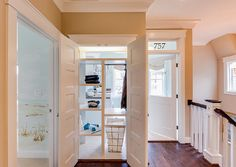 """Laundry Room.  Pass-through shelving accessible both from inside the laundry room and from just outside provides """"get it yourself"""" convenience.  This is such a smart idea! I would love to incorporate it at home. I might would want to make each shelf wider to place laundry baskets. Every family member would have their own shelf. Laundry Room Ideas. #laundryRoom #laundryRoomIdeas"""
