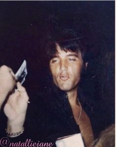 Elvis signing autographs at the gates of Graceland.