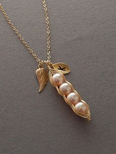 This necklace features a peach swarovski pearl that has been hand wrapped with tarnish resistant gold wire to create an adorable pea pod charm. Shop: www.foxandfigs.etsy.com