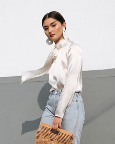 Twist on a classic white blouse styled with vintage levis and statement earrings. Getting major french girl style vibes with the Saint Laurent bow and Cult Gaia bag.