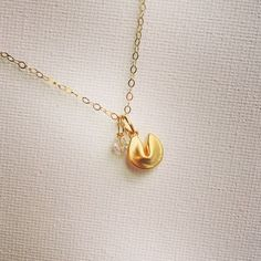 "The Golden Fortune Necklace Just about the cutest thing I've seen - a tiny golden fortune cookie with a tiny Swarovski iridescent (AB) coated clear bicone crystal charm. The cookie is gold plated and the 18"" chain is 14k gold filled. New, no tags. Jewelry Necklaces"
