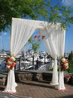 Beautiful fabric arch on the harbor with a chandelier and two floral arrangements on the poles by Sharon Elizabeth's Floral Designs in Berlin, CT