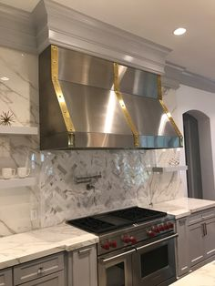 Handcrafted Custom Brushed Finish Stainless Steel Vent Hood with Brass Trim Bands #venthoods #luxurykitchens #customkitchens #interiordesign #elegantdesign #interiorarchitecture #handmadeventhoods #stainlesssteelhood #dreamkitchen #beachsheetmetal
