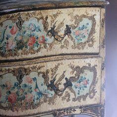 Commode en bois peint à fond beige à décor en léger relief de réserves dorées et argentées composées de rinceaux feuillagés et de fleurs au centre bouquet de fleurs et oiseaux polychromes. Pieds cambrés à sabots feuillagés. Dessus peint à l'imitation marbre. Sicile, milieu XVIIIe.