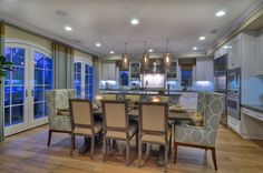 Light gold upholstered chairs surround a distressed wood dining table with sea green upholstered arm chairs at each end.  Finished carpentry adds elegance to the setting.  www.detailsadesignfirm.com #detailsadesignfirm #detailsdesignfirm #diningroom #formaldining