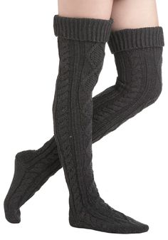Let these long, cable-knit grey socks keep you warm as you flit from one friend's hearth to another this holiday season. When there are parties to attend, a super-cute pair of warming legwear can help you feel at home, and is as essential as eggnog or cookies. Slip these substantial thigh-highs over your favorite pair of bright tights and into a pair of slouchy brown boots.