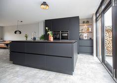 Door een verbouwing ontstond ruimte voor een kookeiland met spoelgedeelte, een hoge kastenwand en een koffiecorner in deze zwarte keuken. De fenix fronten zijn net als het keramiek keukenblad in het zwart uitgevoerd. Een gedurfde keuze, maar door de achtergevel komt voldoende licht naar binnen. Verder beschikt deze greeploze keuken uit Neff apparaten, waaronder twee ovens en een inductiekookplaat met flexzones en bladafzuiging. Ook heeft deze moderne keuken een RVS Quooker Flex met… Kitchen Interior, New Kitchen, Kitchen Decor, Küchen Design, House Design, Kitchen Workshop, Kitchen Organization, Home Kitchens, Decoration