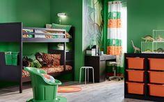 Pokój dla dzieci z czarnym piętrowym łóżkiem, biurkiem, miejscem do przechowywania oraz tekstyliami w kolorze zielonym i pomarańczowym.