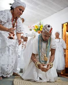 Afro-Brazilians Umbanda religious devotee young boy being assisted in ancestral spiritual ritual.