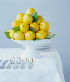 Create a spring centerpiece by filling a cake tray with lemons or other fruit.