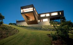 """Residential Architecture: Cape Schanck House by Jackson Clements Burrows: """"..The site is located on a high inland dune amongst dense coastal ti-tree shrub with expansive western views. On approach, the visitor is fronted by an expansive wall which conceals the primary upper level form. The lower level extends from the steep ground plane as a rendered plinth and forms a base much like the surrounding dunes. A winding driveway climbs the steep dune accessing the upper level behind a screen…"""